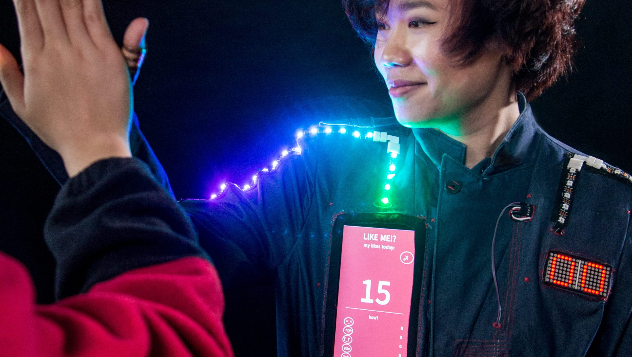 A MonthOfMaking project: Someone wearing a wearable tech project featuring LEDs, a two-digit LED matrix, and a tablet screen. The person is high-fiving someone who is out of view.