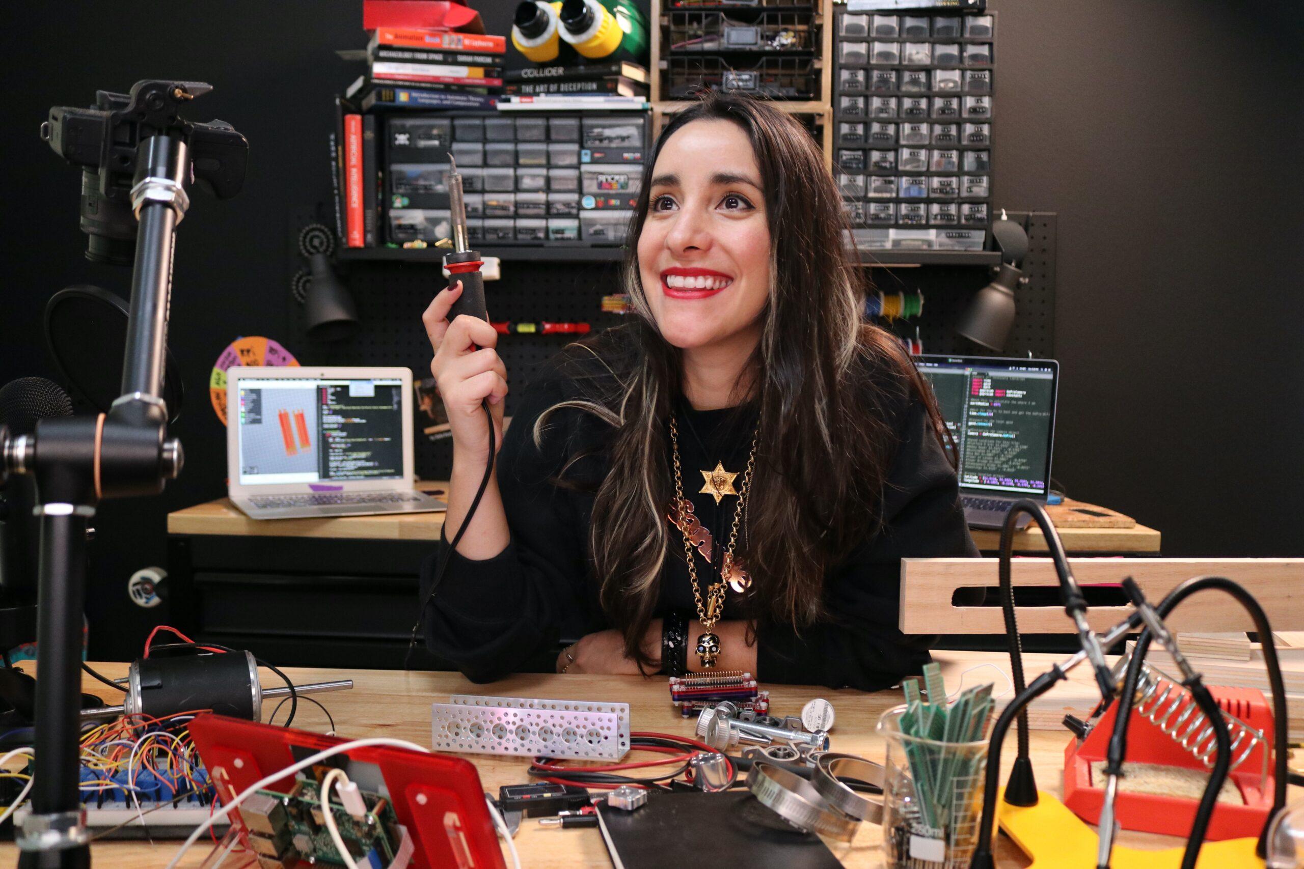 Estefannie with soldering iron at her desk