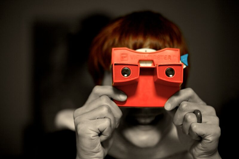 woman holding a view master toy up to her face to look through it