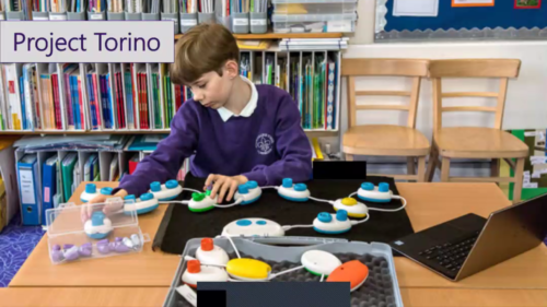 A boy creates a computer program using the Torino tool. There are several Torino pods attached to each other and the boy is using his hands to follow the sequence of the program as it runs.