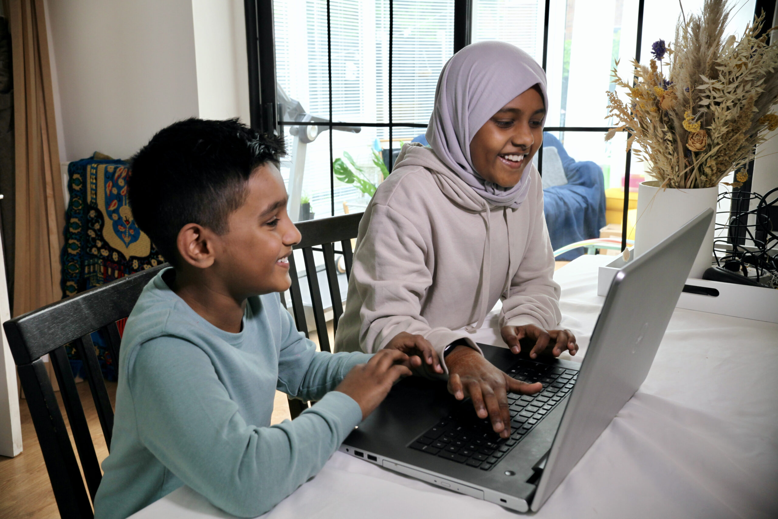 A girl and boy smiling while doing digital making at a laptop