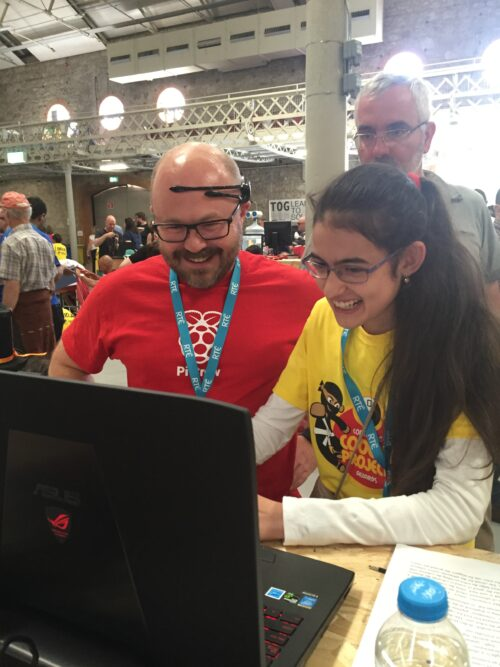 At a Coolest Projects event, a teenage girl tests out her mind-controlled robot at a laptop with a man.