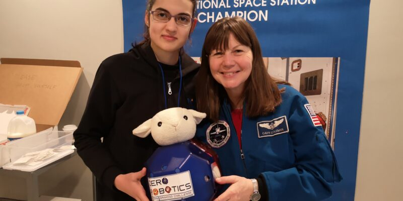 A teenage girl and NASA astronaut Catherine Grace Coleman hold a robot with a toy sheep's head.