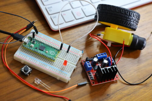 On a wooden desktop, electronic components, a Raspberry Pi Pico, and a motor next to a keyboard.