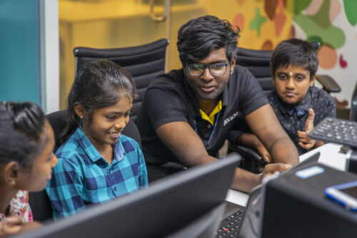 Three young people learn coding at laptops supported by a volunteer at a CoderDojo session.