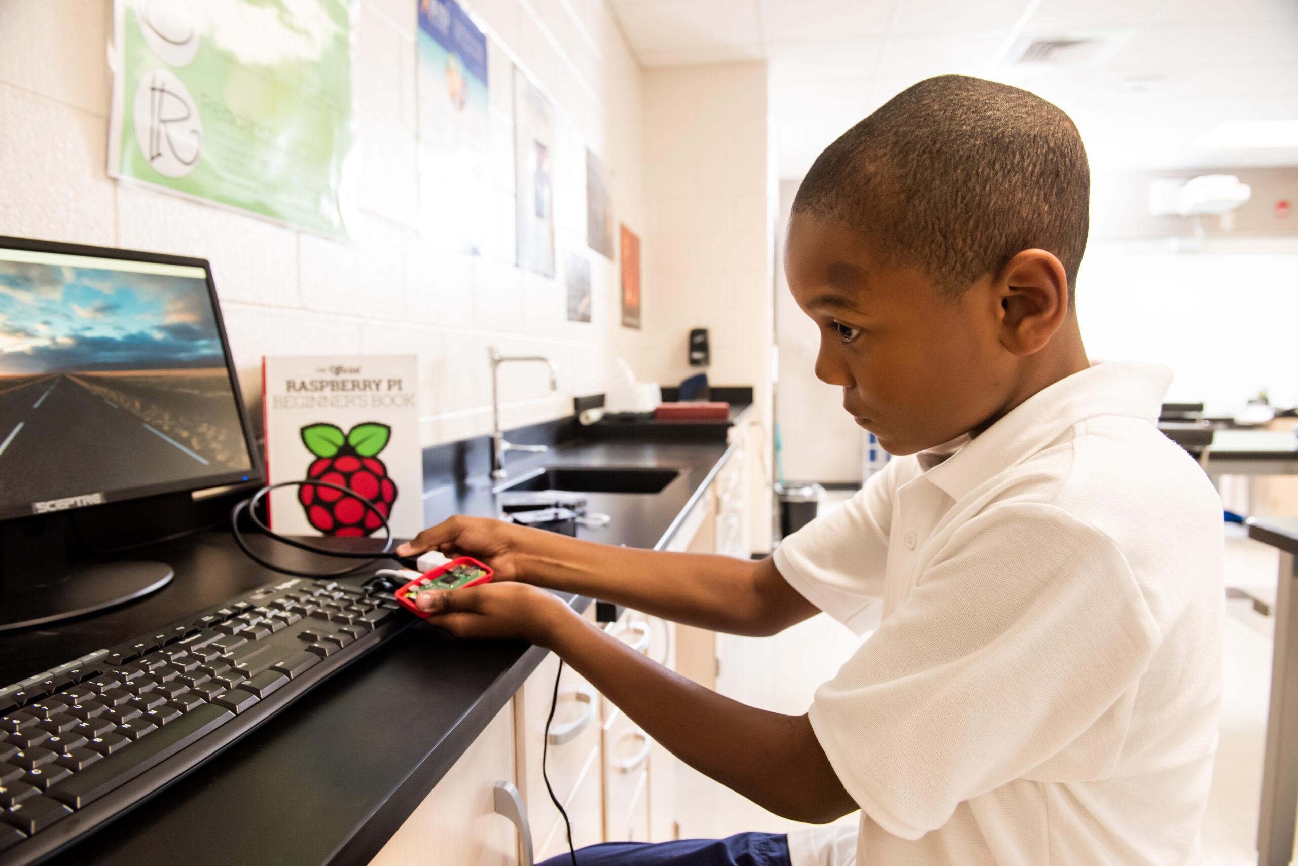 A Black boy uses a Raspberry Pi computer at school.