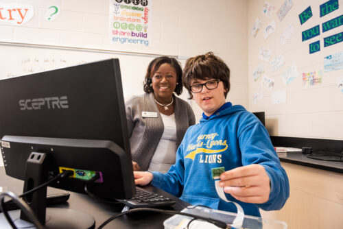 A woman teacher helps a young person with a coding project.