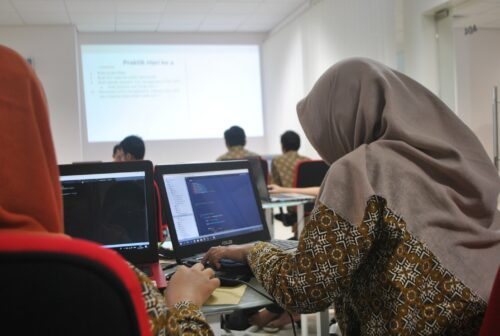 A young woman codes in a computing classroom.